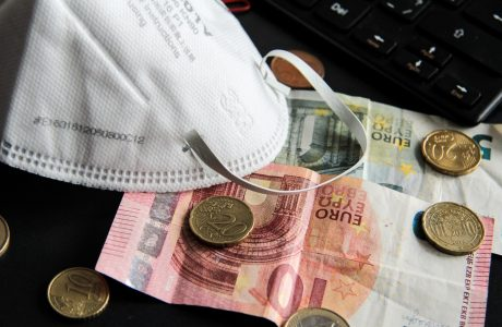 Euro notes and coins and a protective mask